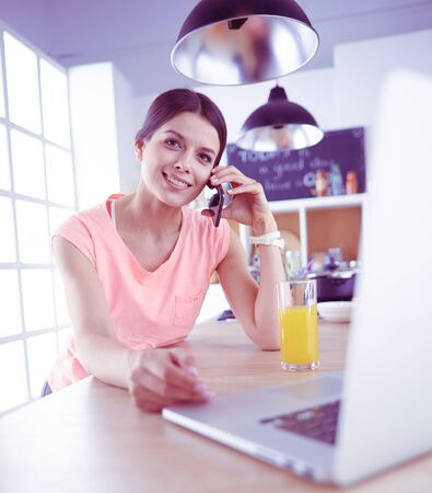 Young woman in kitchen with laptop computer looking recipes, smiling. Food blogger concept