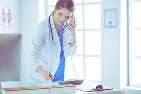 Serious doctor on the phone in her office