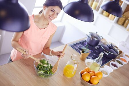 Smiling young woman mixing fresh salad in the kitchen. Stock fotó