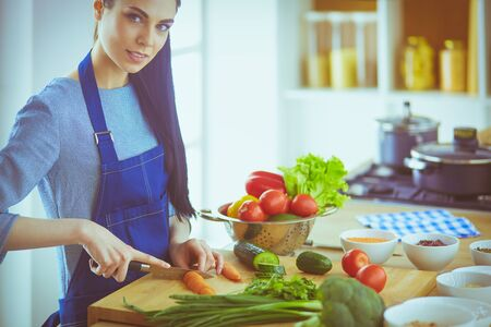 Young woman cutting vegetables in kitchen at home Stockfoto