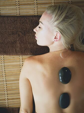 Young woman in spa salon, getting stones massage