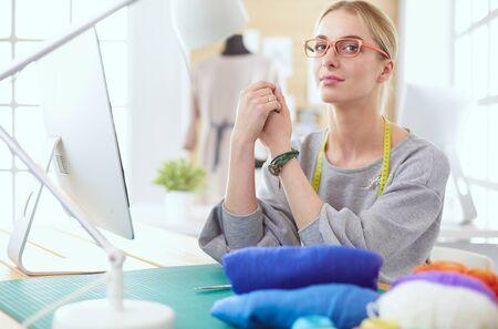 Fashion designer working on her designs in the studio Фото со стока