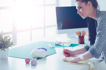 Fashion designers working in studio standing near desk