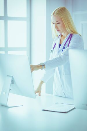 Young woman doctor at work while pointing at computer in hospital office. Stock Photo