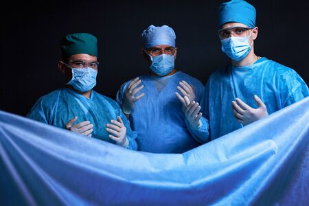 Group of surgeons at work in operating theater toned in blue. Medical team performing operation