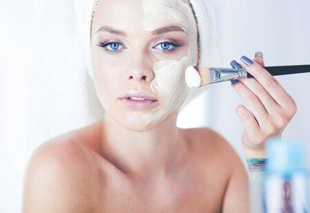 Ein Bild einer jungen Frau, die Gesichtspuder im Badezimmer aufträgt