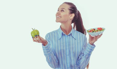 Portrait of a beautiful woman doctor holding a plate with fresh vegetables and green apple. Woman doctor