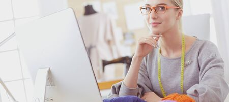 Fashion designer woman working in studio, sitting at thhe desk Фото со стока