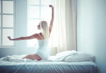Woman stretching in bed after wake up, back view Stok Fotoğraf