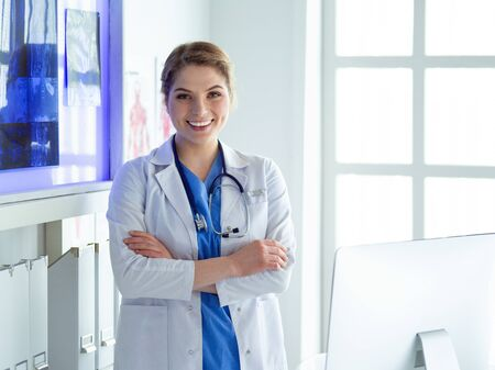 Young woman medic in white uniform standing in clinics office