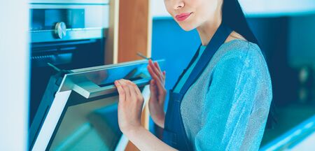 Beautiful young woman checking how her cake is doing in the oven Stock Photo