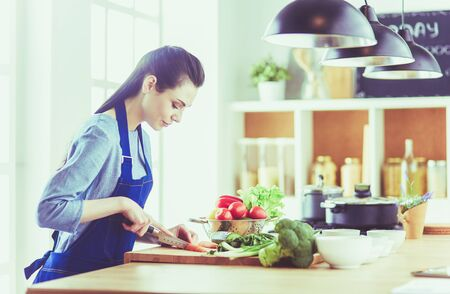 Young woman cutting vegetables in kitchen at home Stock Photo