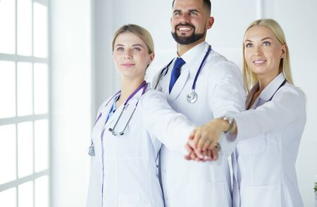 Doctors and nurses coordinate hands. Concept Teamwork in hospital for success work and trust in team