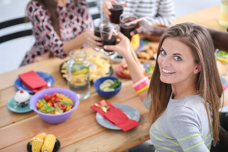 Top view of group of people having dinner together while sitting at wooden table. Food on the table. People eat fast food. Portrait of a girl Stock Photo - 128765544