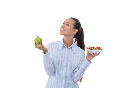 Portrait of a beautiful woman doctor holding a plate with fresh vegetables and green apple. Woman doctor. Stock Photo - 128765550