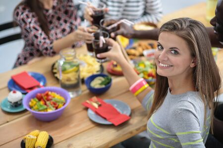 Top view of group of people having dinner together while sitting at wooden table. Food on the table. People eat fast food. Portrait of a girl Stock Photo - 128765576