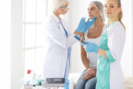 Beautiful woman face near doctor with syringe. Banco de Imagens
