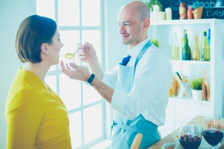 Couple cooking together in the kitchen at home 版權商用圖片 - 128765656