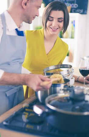 Attractive couple in love cooking and opens the wine in the kitchen while they cook dinner for a romantic evening Stock Photo