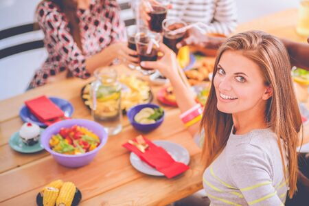 Top view of group of people having dinner together while sitting at wooden table. Food on the table. People eat fast food. Portrait of a girl Stock Photo - 128765701