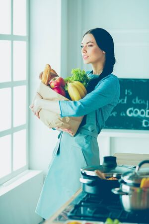 Young woman holding grocery shopping bag with vegetables Stock Photo - 128765841