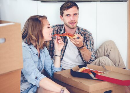 Young couple have a pizza lunch break on the floor after moving into a new home with boxes around them.