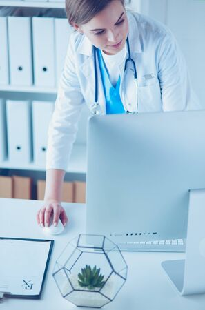 Portrait of female physician using laptop computer while standing near reception desk at clinic or emergency hospital Imagens