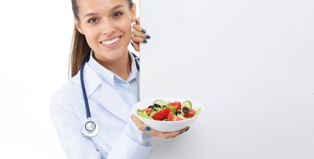 Portrait of a beautiful woman doctor holding a plate with fresh vegetables standing near blank. Woman doctors