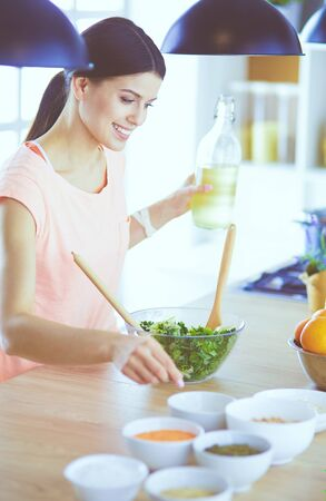 Smiling young woman mixing fresh salad in the kitchen. Stock Photo