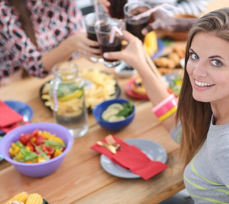 Top view of group of people having dinner together while sitting at wooden table. Food on the table. People eat fast food. Portrait of a girl Stock Photo - 128766383