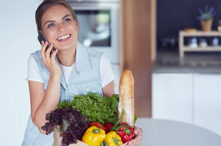 Smiling woman with mobile phone holding shopping bag in kitchen Stock Photo - 128766406
