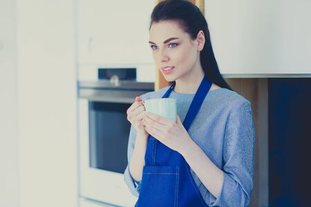 Portrait of young woman with cup against kitchen interior background