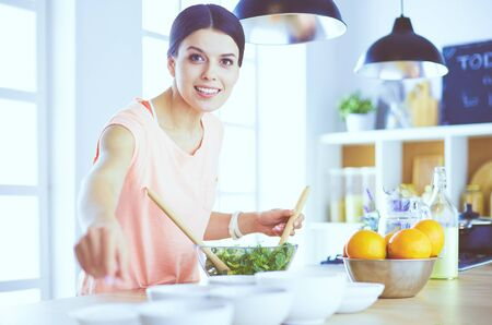 Smiling young woman mixing fresh salad in the kitchen. Banco de Imagens - 129014074