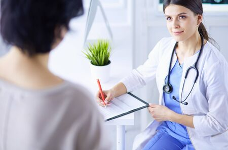 Doctor and patient discussing medical problems in a hospital consulting room. Doc filling in a patients form Stock Photo