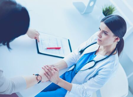 Female doctor calming down a patient at a hospital consulting room, holding her hand Stock Photo - 129148023