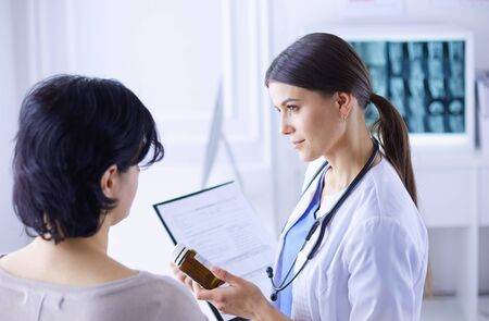 Beautiful female doctor explaining medical treatment to a patient, holding a bottle of medicaments Stock Photo - 129148039