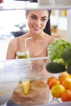 Young woman with glass of tasty healthy smoothie at table in kitchen Standard-Bild - 129460839