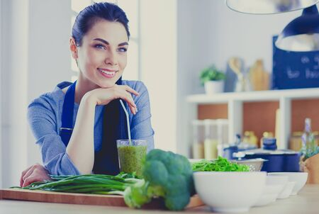 Young woman with glass of tasty healthy smoothie at table in kitchen Standard-Bild - 129460844