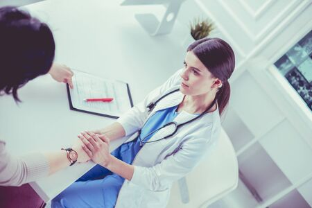 Female doctor calming down a patient at a hospital consulting room, holding her hand