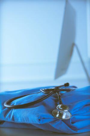 Image of stethoscope and doctor coat on the table in a consultancy room. Medical concept Stok Fotoğraf