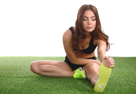 Woman sitting with crossed legs on the green grass. Stock Photo