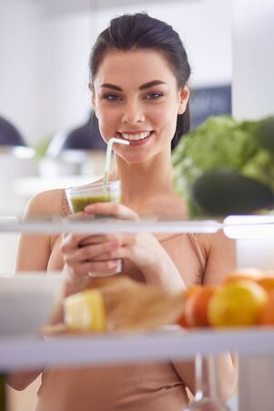 Young woman with glass of tasty healthy smoothie at table in kitchen Standard-Bild - 129461479