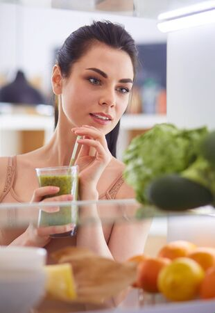 Young woman with glass of tasty healthy smoothie at table in kitchen Standard-Bild - 129462915