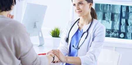 Female doctor calming down a patient at a hospital consulting room, holding her hand Banco de Imagens