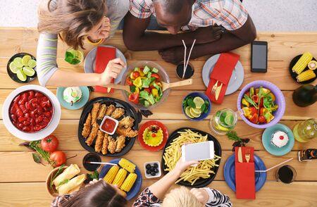 Vue de dessus d'un groupe de personnes en train de dîner ensemble assis à une table en bois. De la nourriture sur la table. Les gens mangent de la restauration rapide.