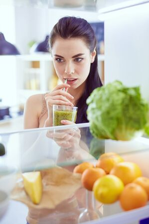 Young woman with glass of tasty healthy smoothie at table in kitchen Standard-Bild - 129463717