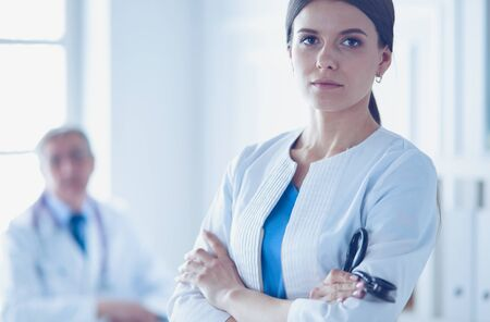 Two doctors in a consulting room in hospital. Female doctor looking at the camera.