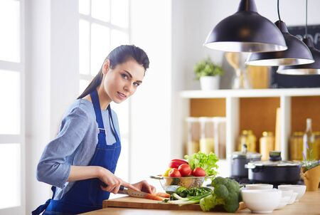 Young woman cutting vegetables in kitchen at home Stock Photo - 129702198