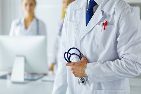 Young male doctor in front of medical group