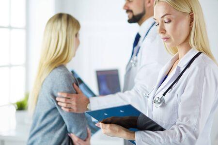 Knappe mannelijke arts die een paar raadpleegt over onvruchtbaarheid in zijn medische kantoor